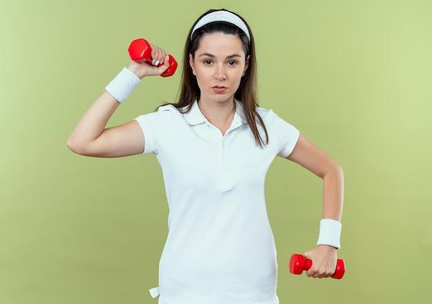 Junge fitnessfrau im stirnband, das mit hanteln mit ernstem gesicht arbeitet, das über lichtwand steht