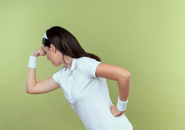 Junge fitnessfrau im stirnband, das müde und erschöpft über hellem hintergrund stehend schaut
