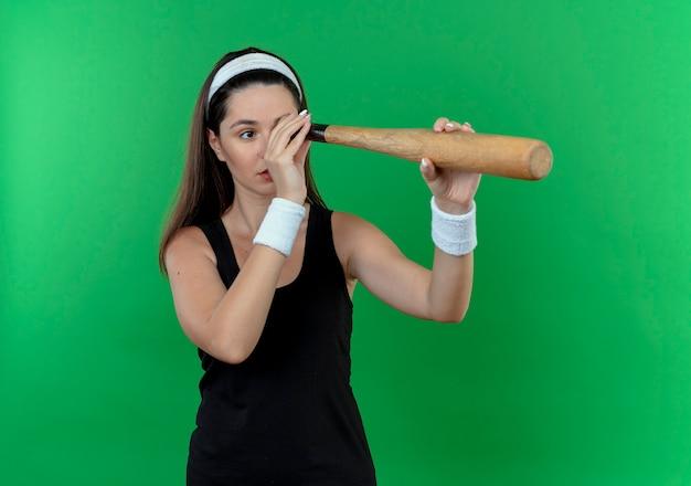 Junge fitnessfrau im stirnband, das über grünem hintergrund steht