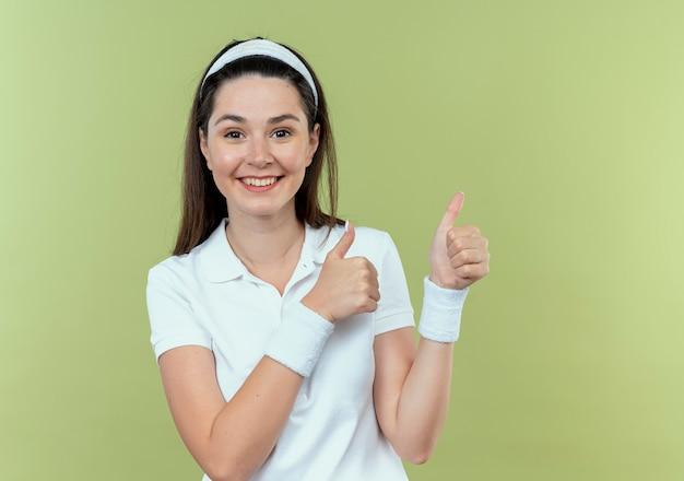 Junge fitnessfrau im stirnband, die fröhlich daumen hoch zeigt, die kamera betrachten, die über hellem hintergrund steht