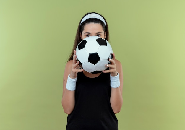 Junge fitnessfrau im stirnband, die fußball hält, der ihr gesicht hinter ball versteckt, der über das stehen über hellem hintergrund späht