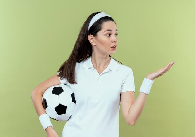 Junge fitnessfrau im stirnband, die fußball hält, der mit arm ihrer hand präsentiert, die überrascht steht, über heller wand stehend