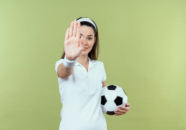 Junge fitnessfrau im stirnband, die fußball hält stoppschild mit hand lächelnd über heller wand stehend hält