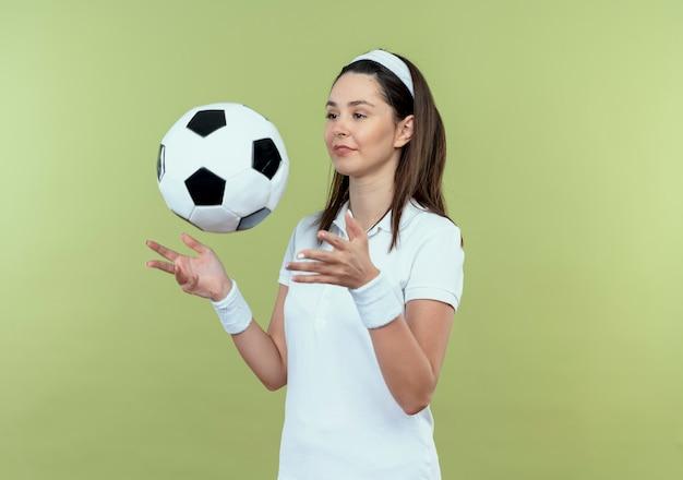Junge fitnessfrau im stirnband, die fußball lächelnd zuversichtlich über hellem hintergrund stehend wirft