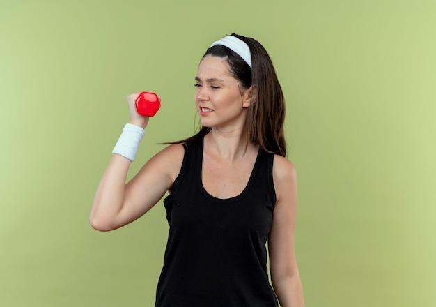 Junge fitnessfrau im stirnband, die hand mit der hantel anhebt, die über der hellen wand angespannt und zuversichtlich steht