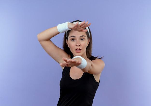 Junge fitnessfrau im stirnband, die ihre hände mit dem selbstbewussten ausdruck über der blauen wand streckend ausdehnt