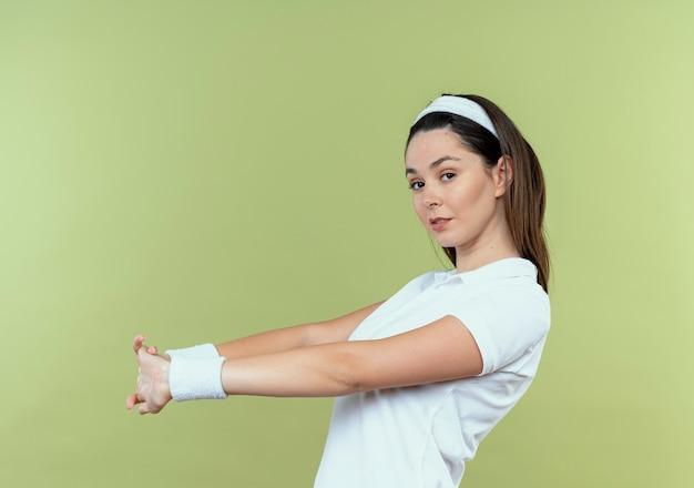 Junge fitnessfrau im stirnband, die ihre hände streckt, die sicher stehen über heller wand stehen