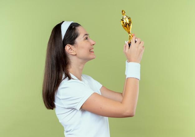 Junge fitnessfrau im stirnband, die ihre trophäe glücklich und aufgeregt betrachtet, die über hellem hintergrund steht