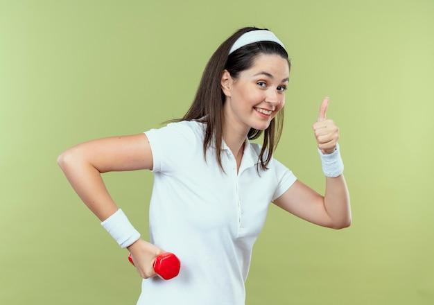 Junge fitnessfrau im stirnband, die mit hantel arbeitet, die kamera lächelnd zeigt, zeigt daumen hoch stehend über hellem hintergrund