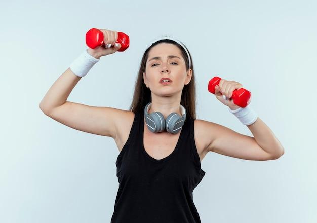 Junge fitnessfrau im stirnband, die mit hanteln arbeitet, die müde stehen über weißem hintergrund stehen