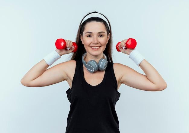 Junge fitnessfrau im stirnband, die mit hanteln arbeitet, die sicher lächelnd über weißem hintergrund stehend schauen