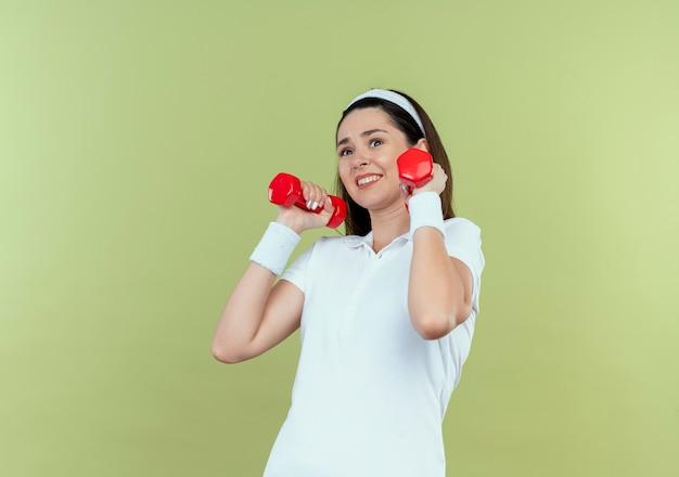 Junge fitnessfrau im stirnband, die mit hanteln arbeitet, die verwirrt stehen über hellem hintergrund stehen