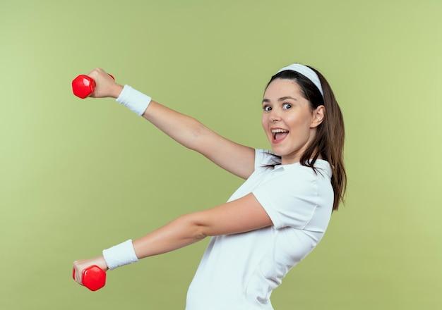 Junge fitnessfrau im stirnband, die mit hanteln herausarbeitet, die fröhlich glücklich und positiv lächeln über hellem hintergrund lächeln
