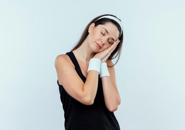 Junge fitnessfrau im stirnband, die schlafgeste mit palmen macht, die kopf auf palmen mit geschlossenen augen lehnen, die über weißem hintergrund stehen