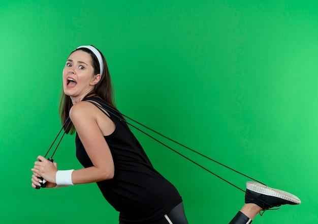 Junge fitnessfrau im stirnband, die springseil hält, das verwirrt und überrascht über grüner wand steht