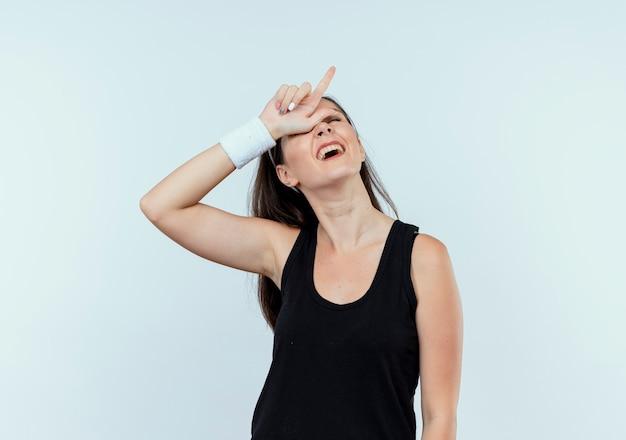 Junge fitnessfrau im stirnband, die verliererzeichen über ihrem kopf macht, der verwirrt steht über weißer wand steht