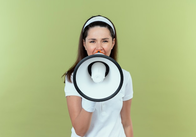 Junge fitnessfrau im stirnband, die zu megaphon schreit, das laut über hellem hintergrund steht