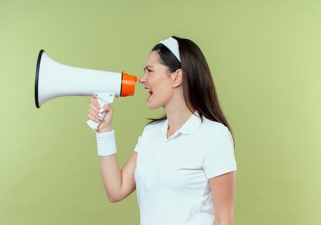 Junge fitnessfrau im stirnband, die zum megaphon mit aggressivem ausdruck schreit, der über hellem hintergrund steht