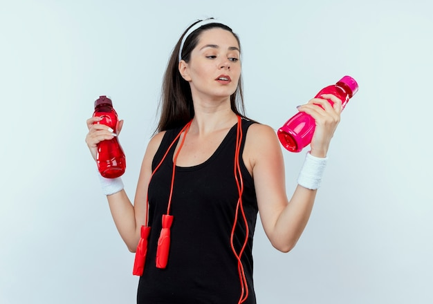 Junge fitnessfrau im stirnband, die zwei flaschen wasser hält, die verwirrt und unsicher stehen über weißer wand stehen