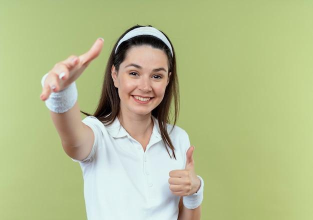 Junge fitnessfrau im stirnband glücklich und positiv, die begrüßungsgeste mit den händen macht, die über lichtwand stehen