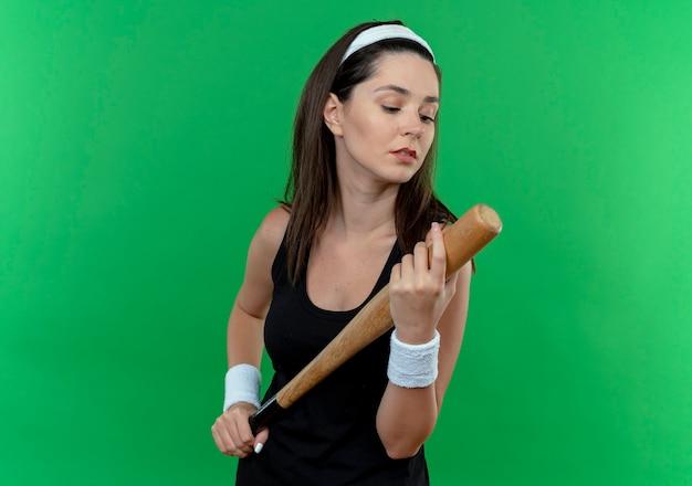 Junge fitnessfrau im stirnband hält baseballschläger, der es mit ernstem gesicht betrachtet, das über grüner wand steht
