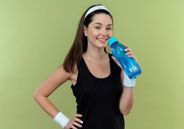 Junge fitnessfrau im stirnband hält flasche wasser lächelnd mit glücklichem gesicht, das über lichtwand steht