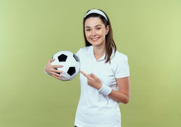 Junge fitnessfrau im stirnband hält fußball, der mit dem finger darauf zeigt, der fröhlich über der hellen wand stehend lächelt