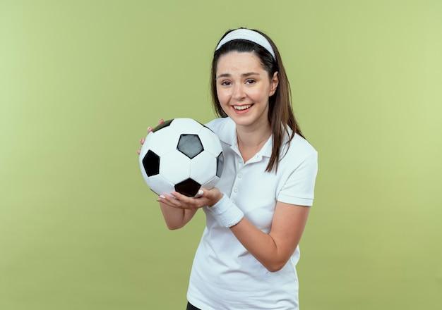 Junge fitnessfrau im stirnband hält fußball lächelnd fröhlich stehend über lichtwand