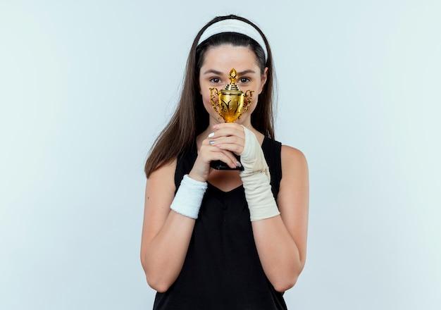 Junge fitnessfrau im stirnband hält ihre trophäe glücklich und positiv lächelnd fröhlich stehend über weißem hintergrund
