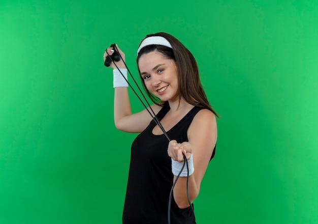 Junge fitnessfrau im stirnband hält springseil lächelnd fröhlich stehend über grüner wand