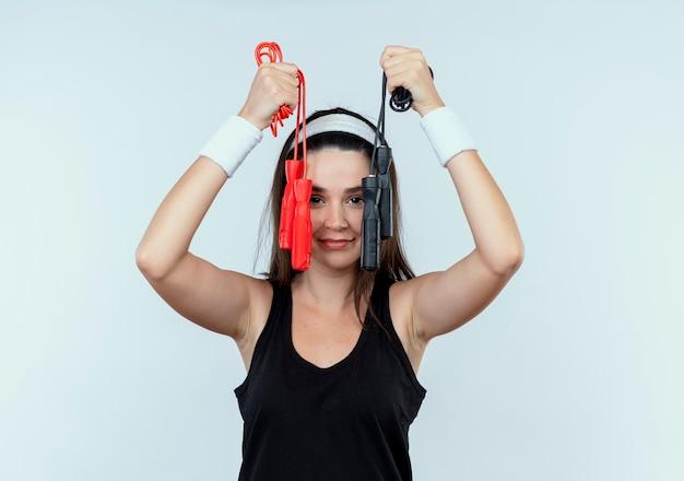 Junge fitnessfrau im stirnband hält springseil mit lächeln auf gesicht, das über weißer wand steht