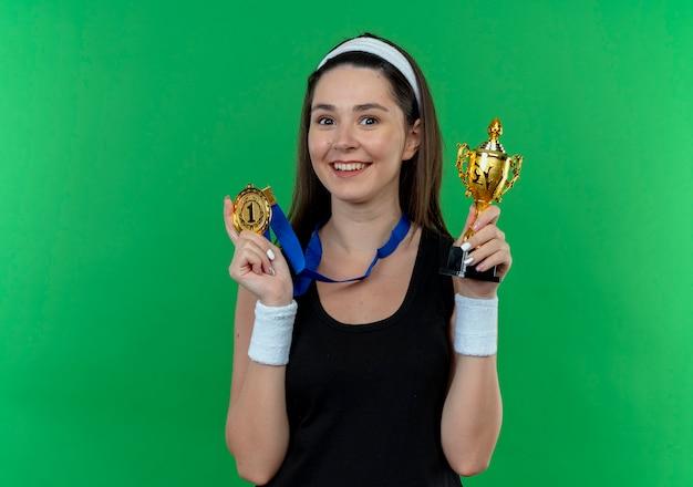 Junge fitnessfrau im stirnband mit goldmedaille um ihren hals hält trophäe lächelnd mit glücklichem gesicht, das über grüner wand steht