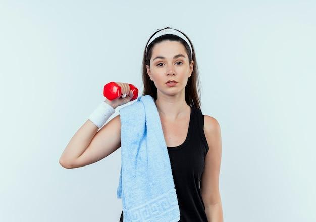 Junge fitnessfrau im stirnband mit handtuch auf ihrer schulter, die mit der hantel arbeitet, die zuversichtlich steht, über weißer wand zu stehen