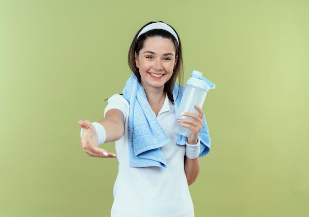 Junge fitnessfrau im stirnband mit handtuch um den hals hält flasche wasser machen hier geste mit lächelnder hand, die über hellem hintergrund steht