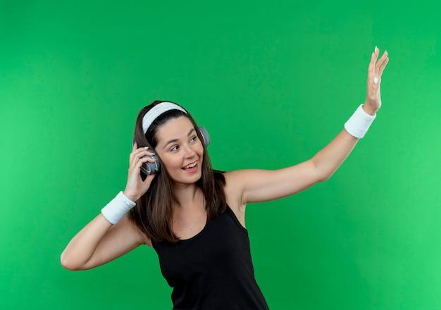 Junge fitnessfrau im stirnband mit kopfhörern, die beiseite lächelnd fröhlich winkend mit einer hand schauen, die über grüner wand steht
