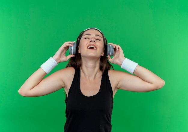 Junge fitnessfrau im stirnband mit kopfhörern, die glücklich und positiv ihre lieblingsmusik genießen, die über grüner wand steht