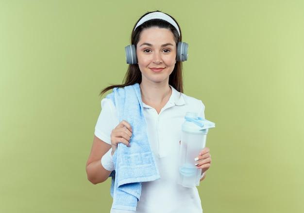 Junge fitnessfrau im stirnband mit kopfhörern und handtuch auf schulter, die flasche wasser lächelnd steht über heller wand hält