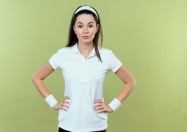Junge fitnessfrau im stirnband mit selbstbewusstem ausdruck mit armen an der hüfte, die über lichtwand stehen