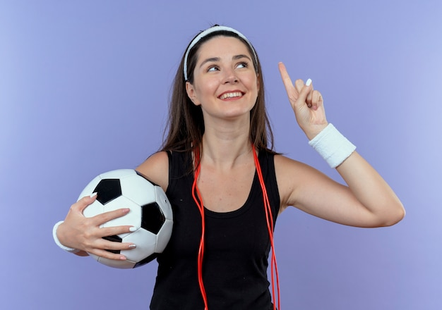 Junge fitnessfrau im stirnband mit springseil um den hals, der fußball zeigt, der oben mit dem finger zeigt, der oben lächelnd neue idee hat, die über blaue wand steht