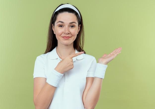 Junge fitnessfrau im stirnband präsentiert etwas mit arm ihrer hand, die mit dem finger zur seite zeigt lächelnd über heller wand stehend