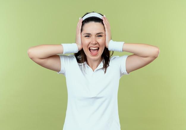 Junge fitnessfrau im stirnband verrückt verrückt schreiend, die ihre ohren mit den händen stehend über der hellen wand schließt