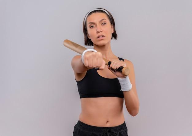 Junge fitnessfrau in der sportbekleidung, die baseballschläger hält, der ihre faust mit ernstem gesicht zeigt, das über weißer wand steht