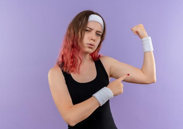 Junge fitnessfrau in der sportbekleidung, die faust zeigt, die bizeps zeigt, der zuversichtlich steht, über lila wand zu stehen