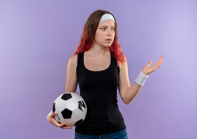 Junge fitnessfrau in der sportbekleidung, die fußball schaut, der verwirrt über lila wand steht