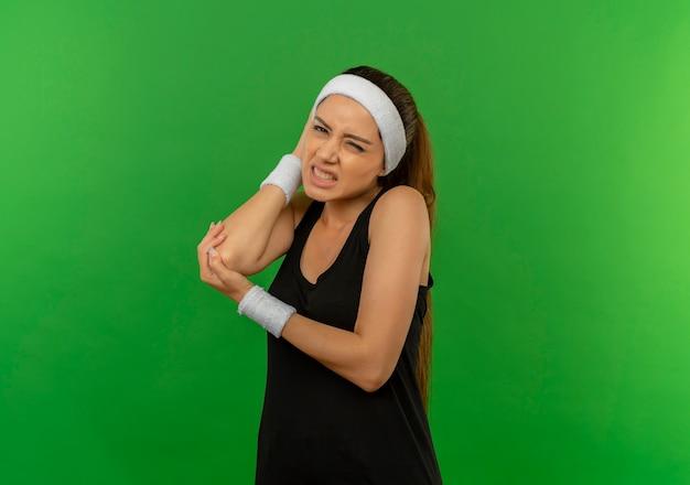 Junge fitnessfrau in der sportbekleidung mit dem stirnband, das den ellbogen berührt, der den schmerz hat, der über grüner wand steht