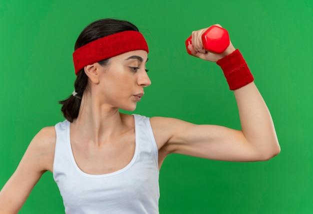 Junge fitnessfrau in der sportbekleidung mit dem stirnband, das die hantel hält, die die hand macht, die die anstrengenden ausschau hält, die über der grünen wand stehen