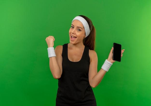 Junge fitnessfrau in der sportbekleidung mit dem stirnband, das die zusammenballende faust des smartphones hält, die fröhlich über grüner wand steht