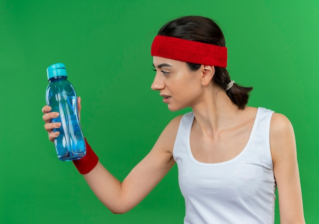 Junge fitnessfrau in der sportbekleidung mit dem stirnband, das flasche wasser hält, die es verwirrt betrachtet, über grüner wand stehend