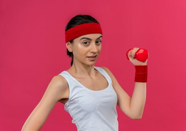 Junge fitnessfrau in der sportbekleidung mit dem stirnband, das hantel in der erhöhten hand hält, die zuversichtlich macht, übungen zu tun, die über rosa wand stehen