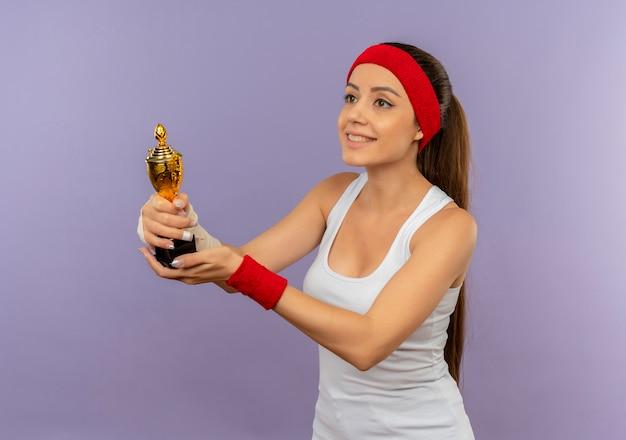 Junge fitnessfrau in der sportbekleidung mit dem stirnband, das ihre trophäe hält, die beiseite wirth glückliches gesicht steht, das über graue wand steht